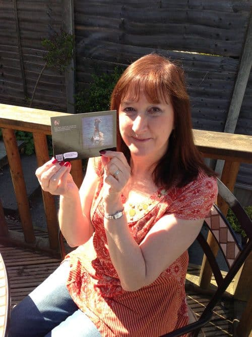 A picture of Simon's mum holding the Postagram she received