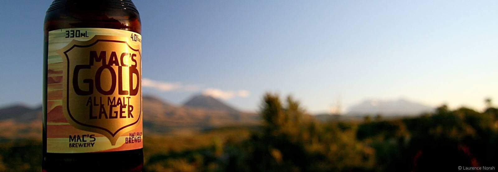 Macs Gold beer bottle with Tongariro National Park in the background