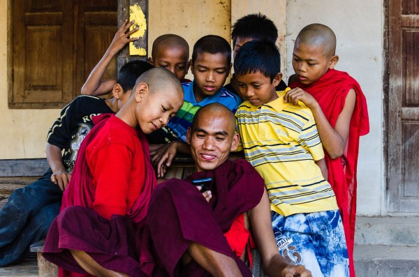 A monk shares a video with a group of kids. © Dustin Main