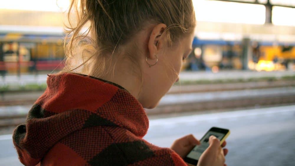 Woman using phone on train platform