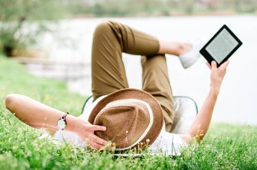 Woman in hat reading Kindle
