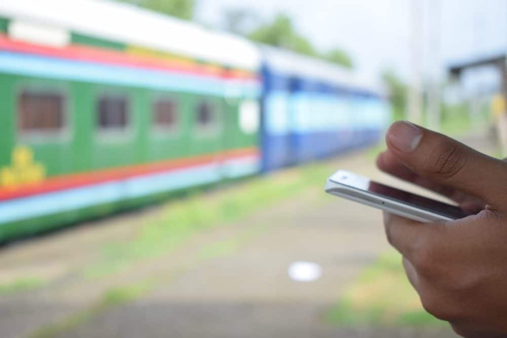 Phone in hands with train in background