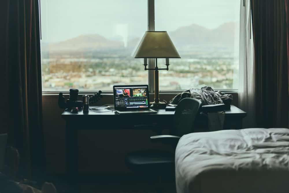 Laptop on table beside window in hotel room