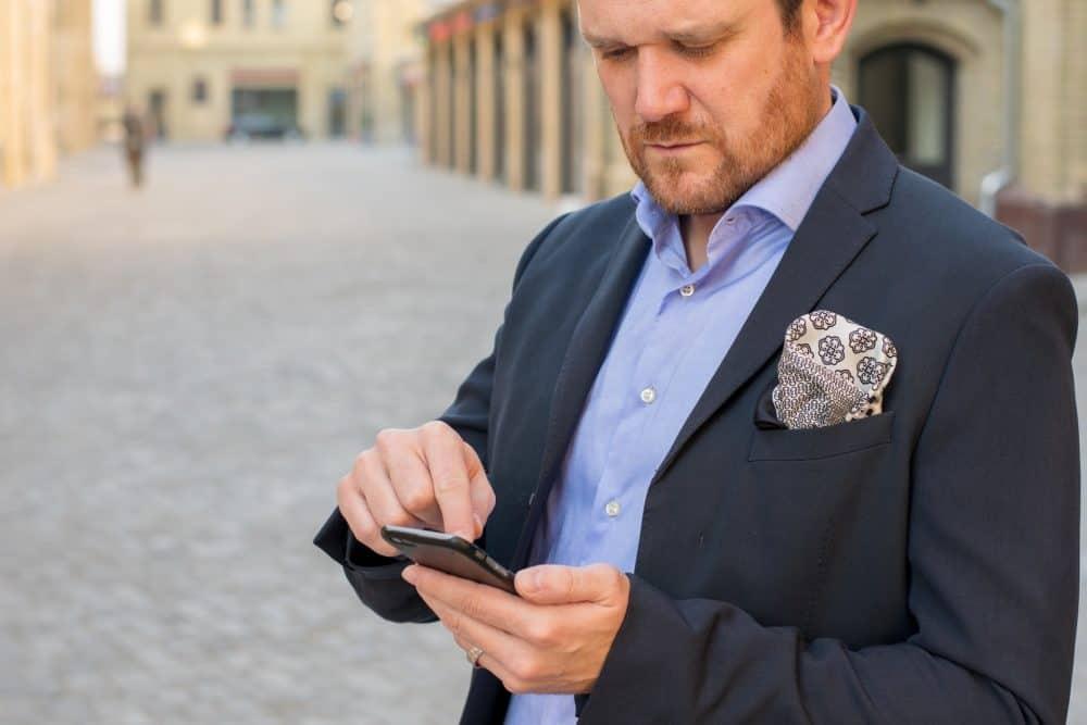 Man in shirt and jacket looking at phone