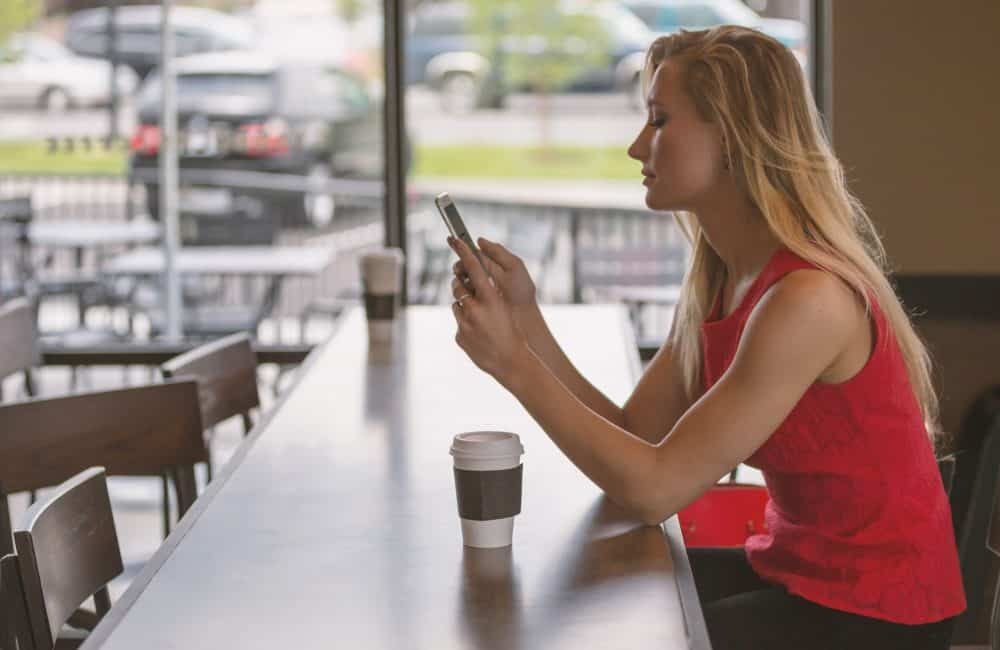 Woman using phone in cafe