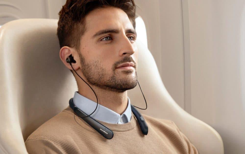 Man on plane wearing Life NC headphones