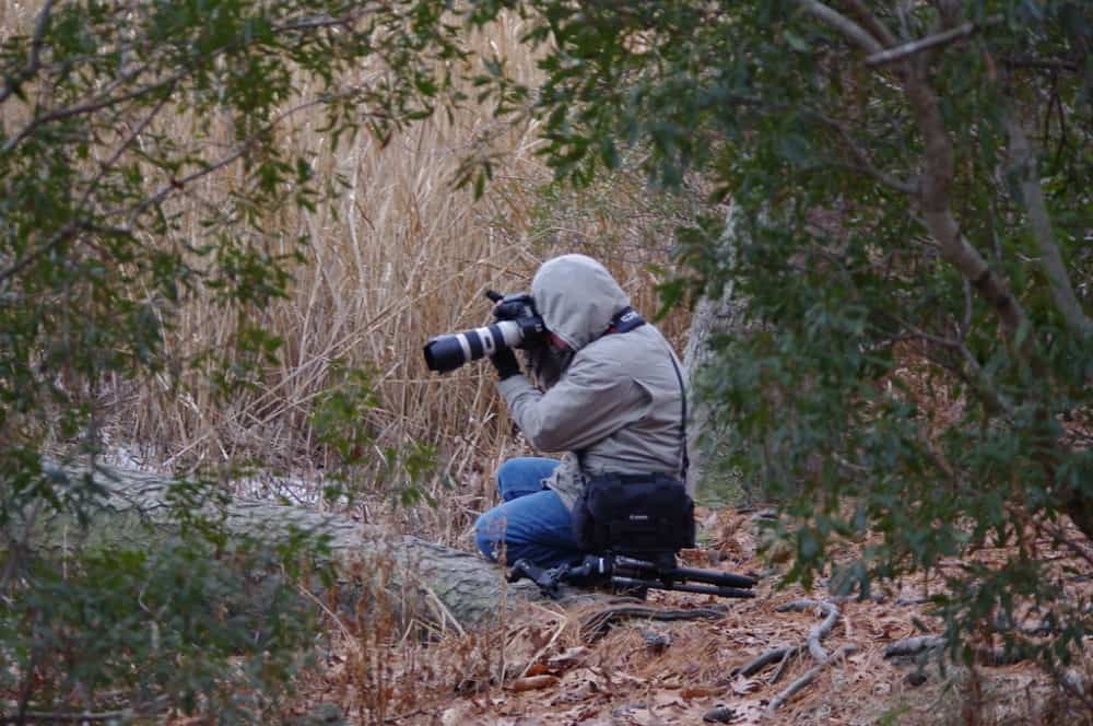Man on dirt trail taking photo