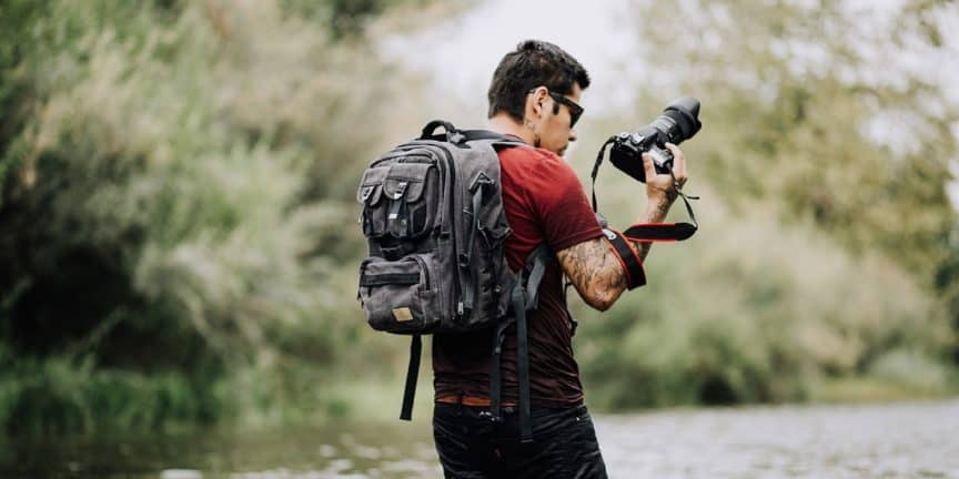 Photographer with backpack beside river