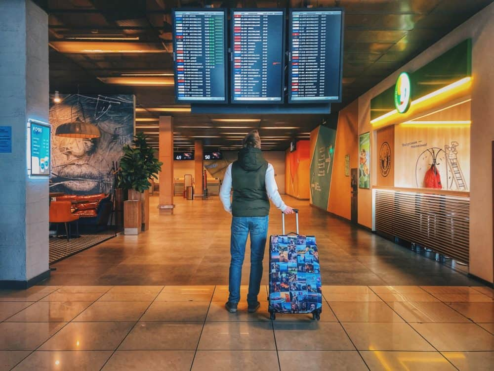 Man with suitcase looking at fight information screens