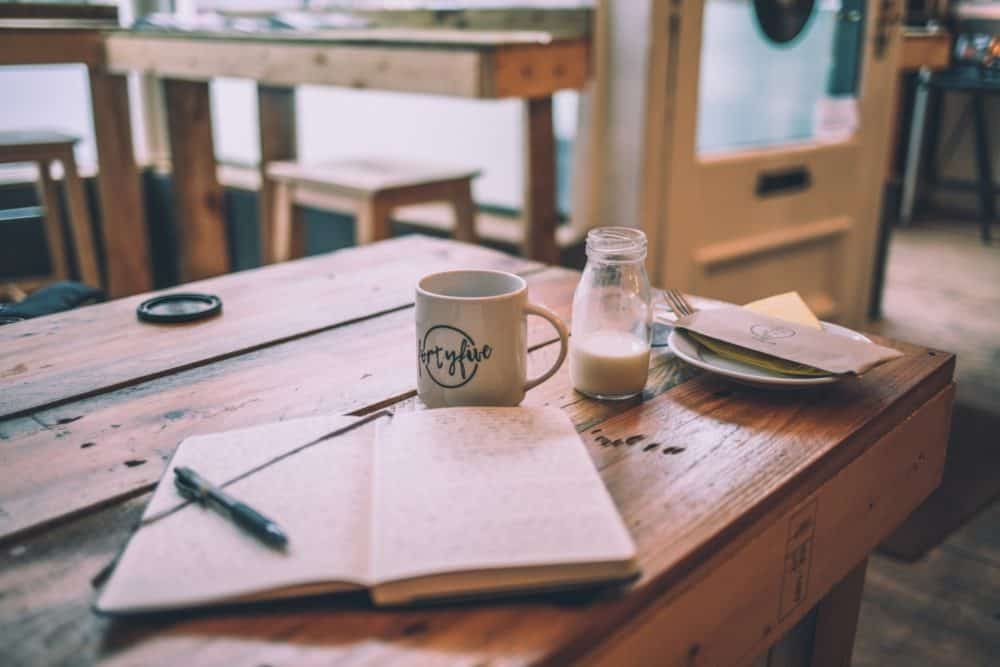 Notebook and cup on table