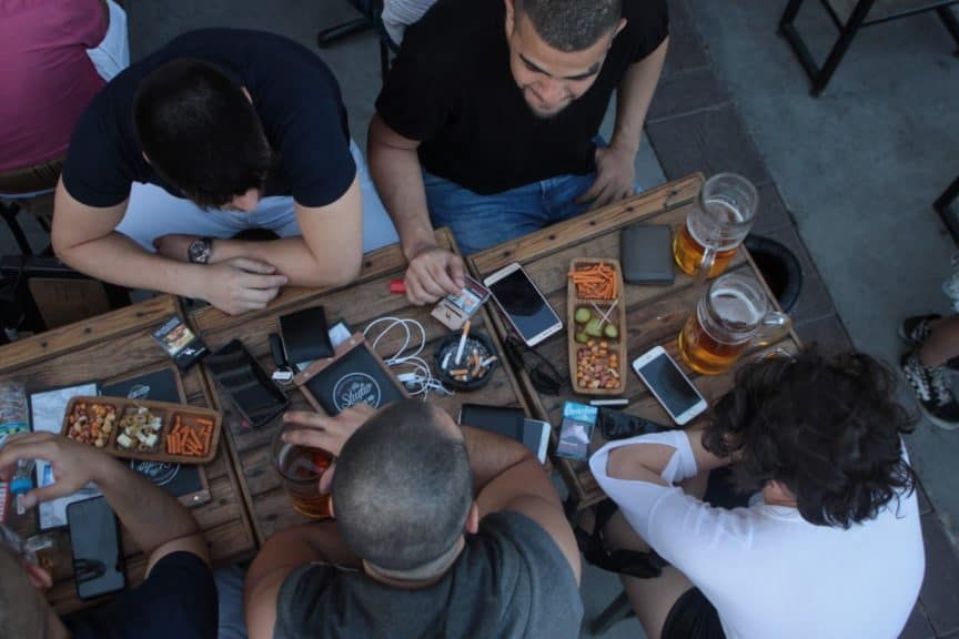 People sitting around table with phones and food