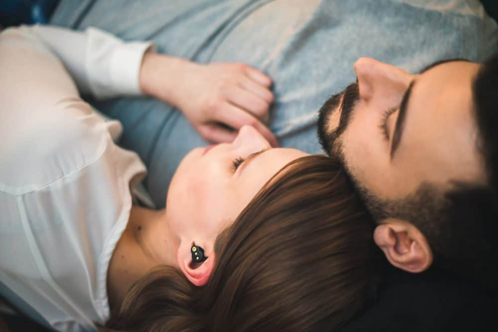 Couple in bed, woman wearing QuietOn earbuds