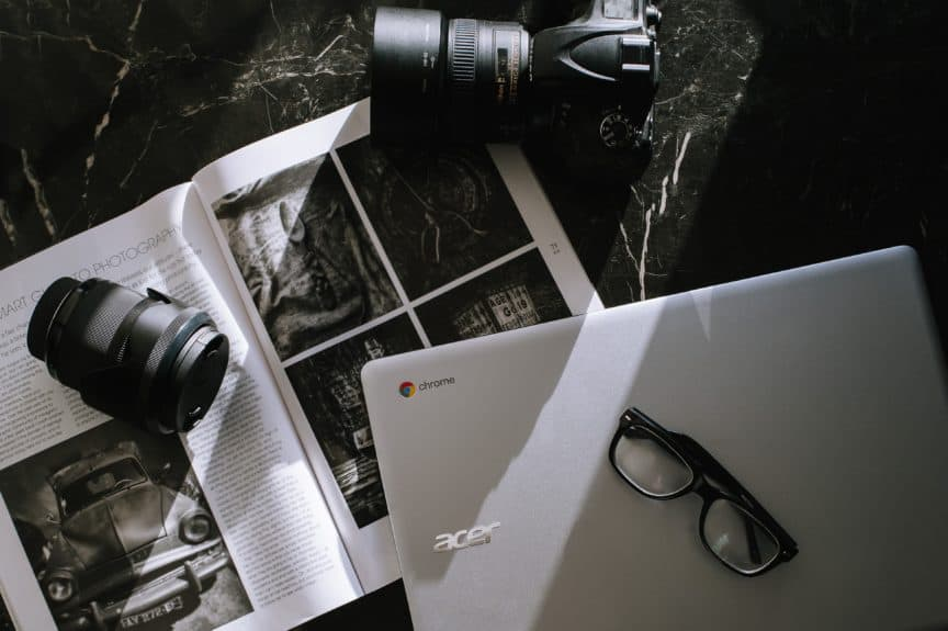 Chromebook, camera and lens, glasses, and book