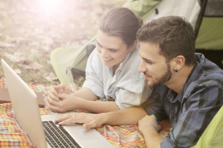 Couple in tent on laptop