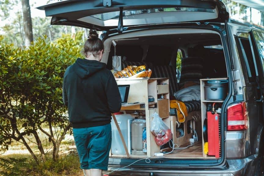Man using laptop at back of campervan