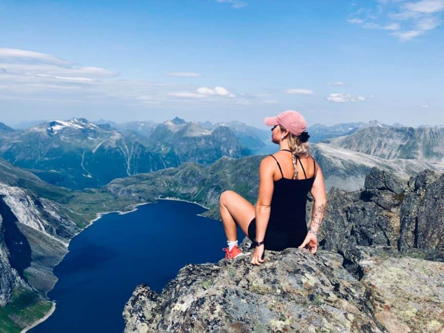 Woman with fitness band on wrist atop mountain