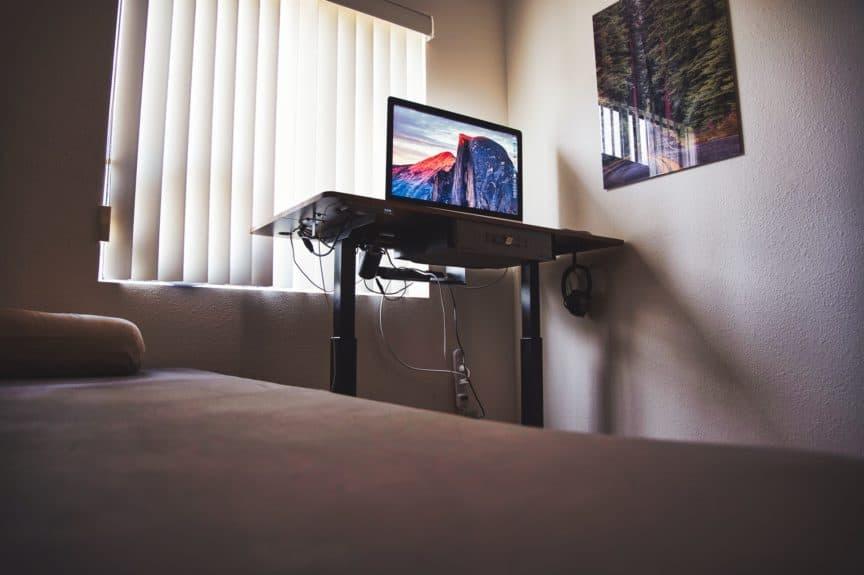 Standing desk beside bed in room