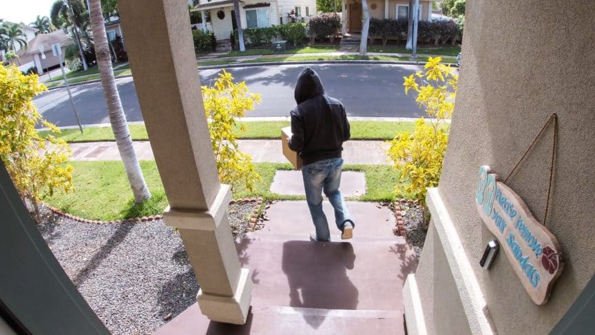 Thief stealing package from doorstep