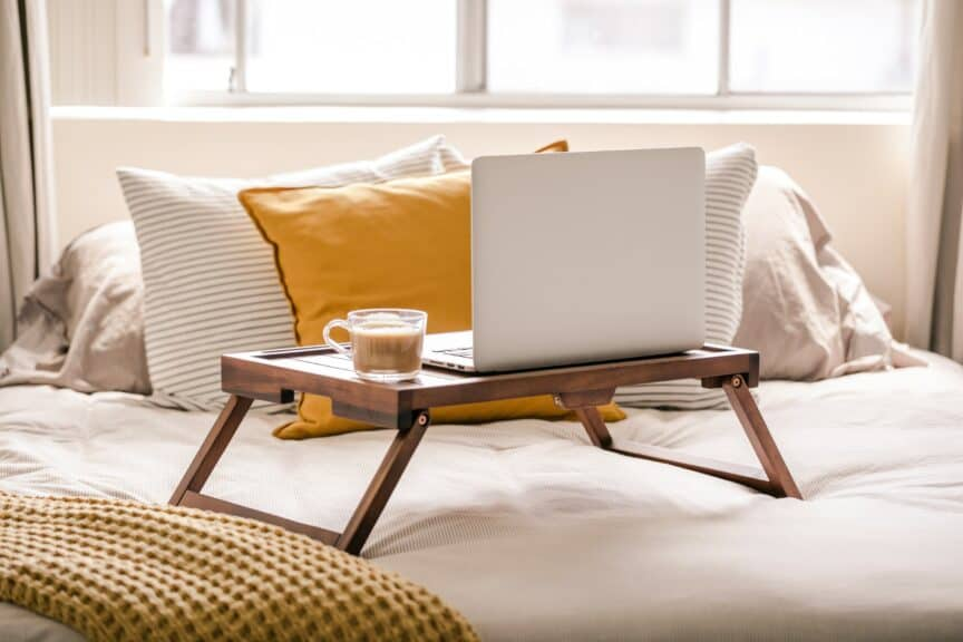 Laptop and coffee mug on table on bed