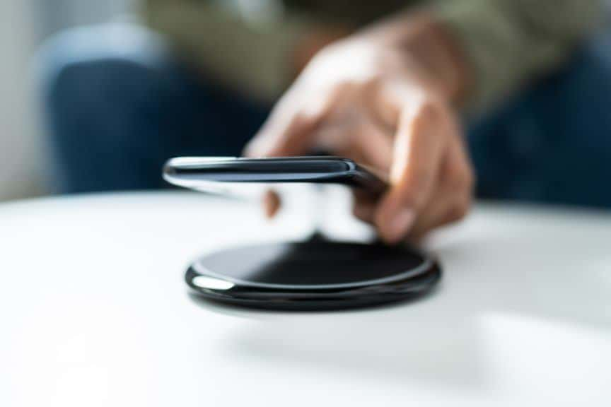 Man putting phone on wireless charging pad