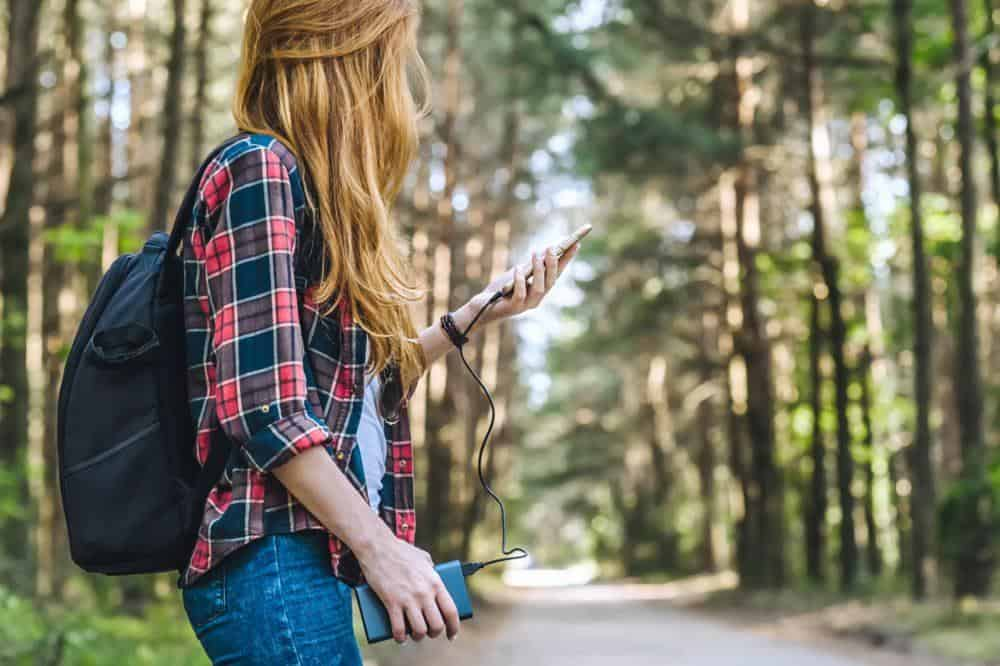 Woman charging phone from power bank in forest
