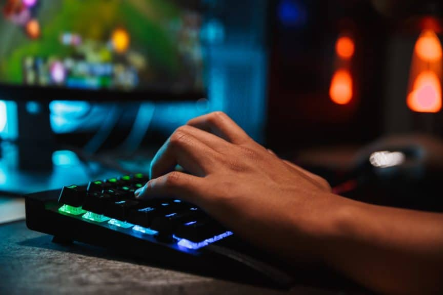 Close-up on keyboard and hand of person playing computer games