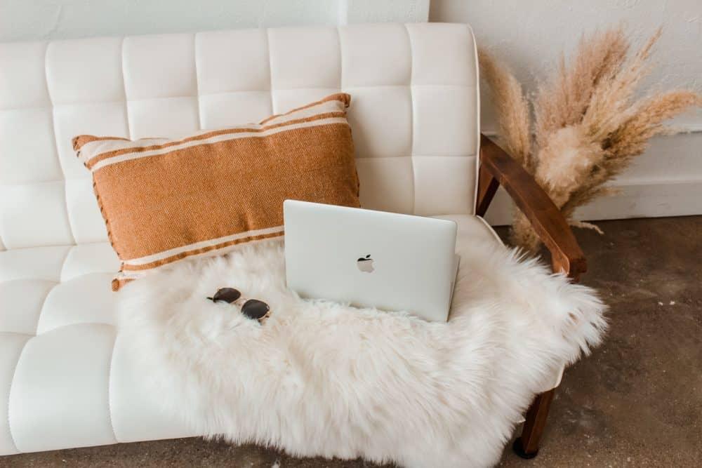 Laptop and sunglasses sitting on white sofa