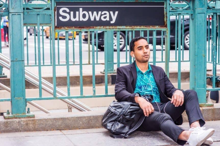 Man sitting under subway sign wearing earbuds