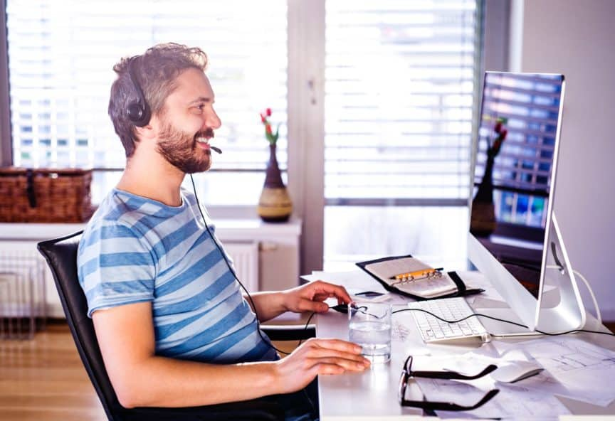 Man sitting in front of computer, working from home and wearing headphones