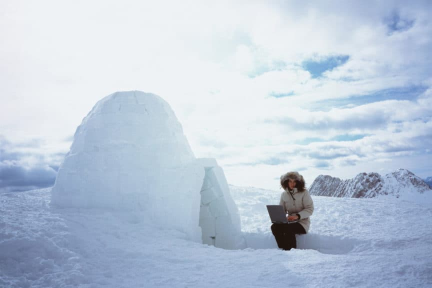 Woman sitting with laptop beside igloo